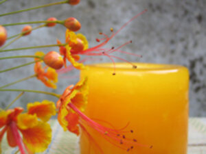 Orange-yellow flowers frame an orange pillar candle