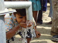 Boy drinking water from a well