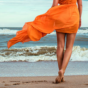 Woman in orange dress at the sea shore