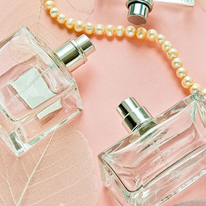 Perfume bottles with pearls over pink background