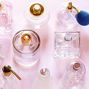 Vintage perfume bottles over pink background
