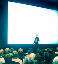 Speaker in front of a bright screen, talkin to a crowd
