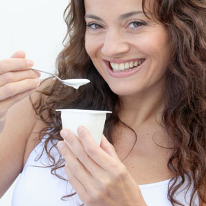 Woman eating yogurt 300