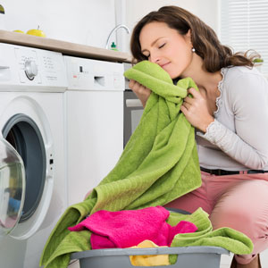 Woman-smelling-clean-laundry-300