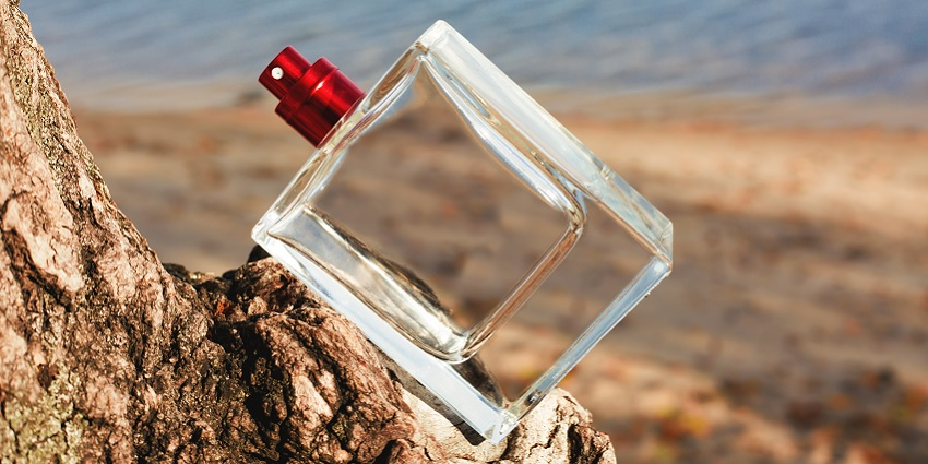 A bottle of perfume next to the ocean