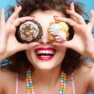 Woman wearing candy necklace with cupcakes over her eyes